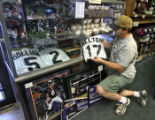 Brett Lehrer (cq) puts a Todd Helton jersey in a show case, Monday afternoon, October 22, 2007, at...