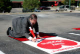 Ray Higgins, Executive Director of the Rocky Mountain Shopping Center Association, signs his own...
