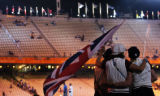 A trio of British athletes hug and watch other athletes walk from the stadium at closing ceremony...