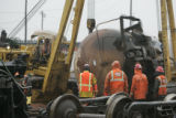 0005 Workers attempt to over turn a tanker after Beer and asphalt spilled out of rail cars near...