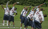(#95) Defensive end Jarvis Moss, second from left, stretches with the team during a Denver Broncos...