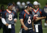 0167 Broncos starting quarterback Jay Cutler, center, stretches with the second string quarterback...