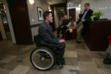 Andy Blood sits in his wheelchair as he is being interviewed while in the background, left to...