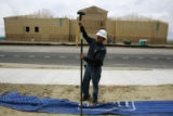 Dan Stansbury (cq), of Delta Construction, puts up a fence at a retail store that is being built...