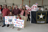 Family and friends of Fort Carson-based Staff Sgt. Matthew Keil wave at the jet as he arrives from...