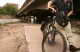 (JOE082) Bicyclist Jack Finch (cq) of Denver turns away from a flooded section of the bike path...