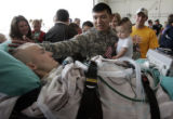 Joseph Camarillo (cq) holds his son Noah Camarillo, seven months, while he greets his friend Staff...