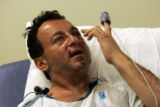 Jerome Stiller (cq), 50, from Golden, talks to reporters from a reclining chair at St. Anthony...