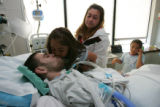 7 year-old Victoria Rangel (cq) kisses her brother Paul Martinez (cq) on his hospital bed at St....