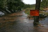 A flood warning sign is posted to a tree on this dirt road in West Creek, May 23, 2007. The...