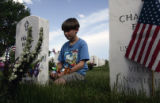 David Merkel, 9 , from Denver visits the grave of his grandfather and grandmother, Frank and...