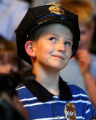 Cancer patient Travis Mickelsen (cq), age 8, looks up at Aurora Police Chief Dan Oates (cq) after...