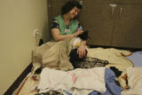 Peggy Risi, (cq), a Veterinary Clinic Volunteer, sits in the recovery corner with a dog on her lap...