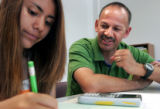 Glenton Muller (cq) a math teacher at Bruce Randolph School,  tutors Angie Hernandez,15 at the...