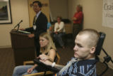Dr. Shih-Fong (Mike) Hsu at the podium at back listens to questions with Tracy holding Matthew's...