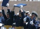 (JOE1347) - A trio of Air Force Academy graduates show off their diploma's to friends and family...