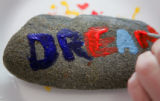 "Hospice patient Karen Foster (cq) paints the word ""dream"" on a rock during an arts and..."