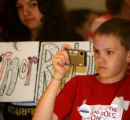 Ethan Callies, 11, of Lakewood, takes pictures while Gov. Ritter signs Senate Bill 36, Wednesday...