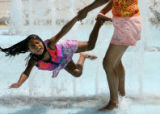 MJM181  Sara Rodriguez (cq), 6, is swung through spouts of water by her mother, Rosa Gomez (cq),...