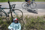 Nancy Ryan (cq) takes a rest and eats some snacks off the side of highway 83, as other cyclists...