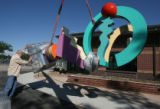 Robert Ellison (cq)  guides   his 14-foot-tall abstract sculpture as it is raised by crain in...