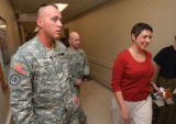 left to right, Sgt. Christopher Smith and Sgt. Michael Cordosi accompany Heather Henniger, holding...