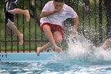 DLM0757  Angelo Benavidez, 10, left (only legs), and L.J. Mendez, 11, leap into the Harvey Park...