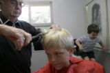 Don Eafanti (cq), of Wheat Ridge, cuts his grandson Kristopher Keelan's, 8, hair at his barber...