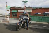 Greg and Suz sit upon Greg's (cq all three) Ultra Classic Harley-Davidson in front of Lincoln's...