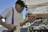 Dennis Hamann(cq), of Denver, Colo, juggles apricots as he pays at Fruit Stand Inc. at the Cherry...