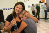 Deana Rambo (cq), gives a hug to her daughter Tyler Rambo (cq), 12, at a meeting for evacuees at...