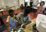 Delriece Taylor, (cq), (left), 8, and Kameron Collier(cq), 9, cut through styrofoam during their...