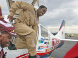 Barrington Irving (cq) climbs out of his Columbia 400 aircraft after landing at the Front Range...