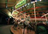 Nicole Radovich,(cq) of Denver rides a zebra, one of the handcarved figures of the carousel at the...