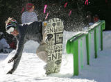 A snow boarder takes a spill off  a double barrel rail on  18 inches of man-made snow on the High...