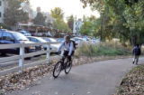 A cyclist passes by Kennedy Ridge, a 1059 unit apartment complex at 10700 E. Dartmouth Avenue on...