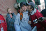 Rockies fan Chris Bianchi (who we followed yesterday) gets a kiss from Red Sox fan David Millette...