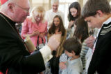 The Cardinal J. Francis Stafford blesses the Cieslak family at a reception at the St. John Vianney...