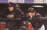 [3561]  Colorado Rockies teammates, including Todd Helton, right, stand dejected in the dugout...