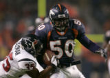 (Denver, Colo., August 27, 2004) Cornelius Anthony is tackled by KaRon Coleman as he runs towards...