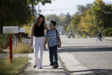 31 year-old Juana Maldonado (cq) walks her son, 8 year-old Andres Marmolejo (cq) back from school...