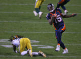 [EPS101]  Denver Bronco wide receiver Brandon Marshall spins out of a tackle by Green Bay safety...