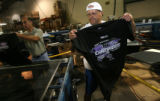 Warehouse manager, Tony Barba, cq,  removes t-shirts from the silkscreen machine and places them...
