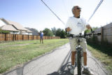 DM0004     Mike Long, 58, stops to talk as he rides his bike down the path in the 1300 block...