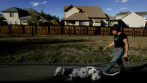 DM0006     Leasa Peterson walks her dog, Sam, down the bike path on the 1300 block between...