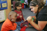 Eighth-grade volunteer Annie Sanchez  (cq), 13, reads to De'Quan Leopold, left, and Micaela Vigil...