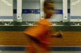 A student from Weber Elementary School in Arvada, Colo., walks past a row of hallway sinks on...