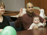 Julia Reichel (cq)   and Rajiv Balsavar (cq) holding their son Keiran take the oath as they appear...