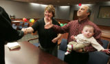 Proud parents Julia Reichel (cq) left  and Rajiv Balsavar (cq) holding their son Keiran are...