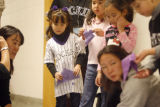 (far left) Lexi Cozzetti (cq) wears her Rockies jersey as she waits to paste her good luck wishes,...